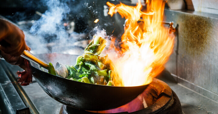 Charred food being cooked in the kitchen inside a wok