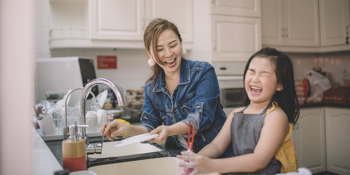 Mother and daughter having fun using life hacks in the kitchen
