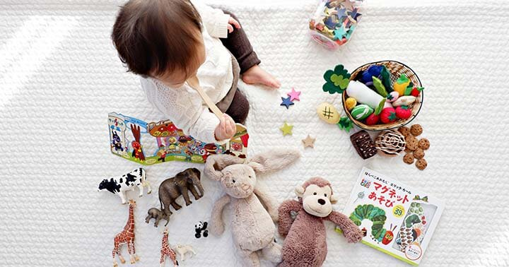 Toddler with various toys