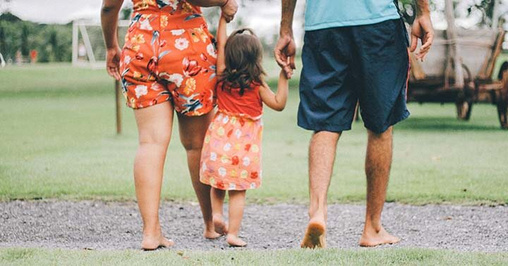 Family of three walking barefooted in a park