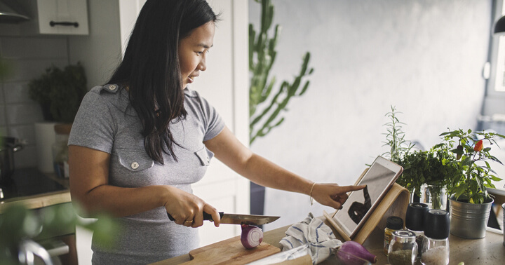 A woman cooking in the kitchen while following instruction on a tablet