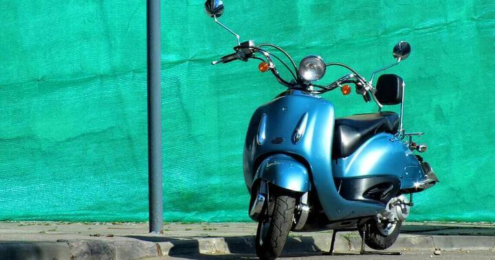 A vespa parked by the roadside